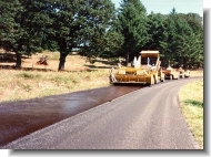 Chip seal spreader applying oil to roadway